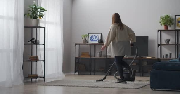 freudige junge Frau putzt Teppich im Wohnzimmer und tanzt mit Staubsauger in Wohnung, glückliche junge Dame drinnen