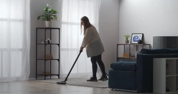 Reinigungsservice, weibliche Arbeiterin reinigt Teppich im Wohnzimmer einer modernen Wohnung mit Staubsauger
