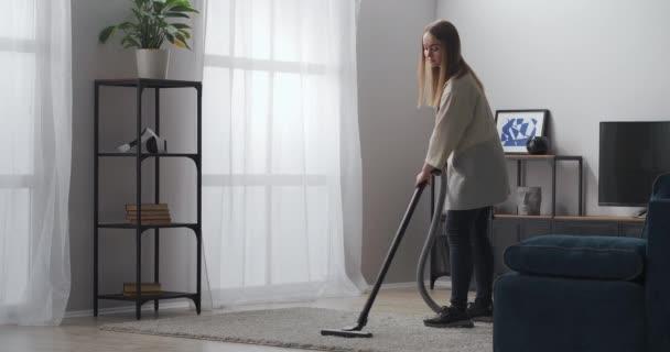 junge Dame saugt Teppich im Wohnzimmer einer modernen Wohnung, steht im Zimmer mit Staubsauger