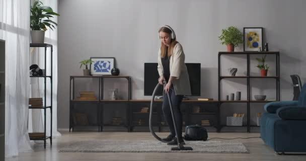 hübsches Teenie-Mädchen macht spielerisch und fröhlich Hausarbeit, saugt Teppich und tanzt, hört Lieder über Kopfhörer