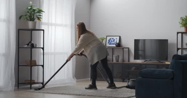 Teppichreinigung mit Staubsauger, Frau erledigt Hausarbeit in moderner Wohnung, Haushaltsgeräte