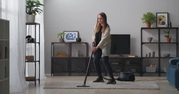 Teenager Mädchen putzt zu Hause und tanzt mit Staubsauger im Wohnzimmer, Spaß und Hausarbeit am Wochenende
