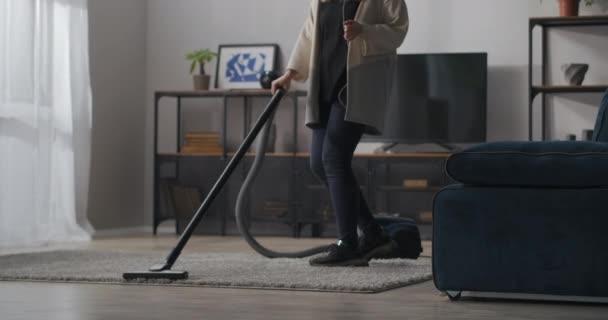 Haushälterin saugt im Wohnzimmer der großen Wohnung, junge Frau hört Musik per Kopfhörer und tanzt, Hauswirtschaft