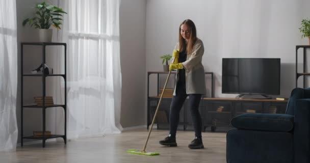 šťastný dospívající dívka je tanec s mop při čištění domova, pomoc kolem domu a mytí podlahy, radost a zábava při domácích pracích