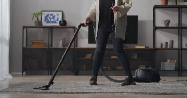Hausfrau putzt Wohnzimmer, staubsaugt und tanzt im Wohnzimmer, Blick auf den unteren Körperteil