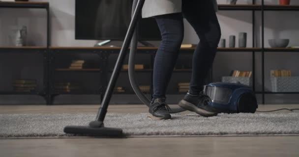 junge Frau tanzt und staubsaugt im Zimmer, putzt zu Hause, Nahaufnahme der Beine auf Teppich und Staubsauger, Hauswirtschaft