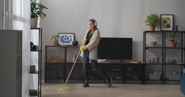 mladá dáma myje podlahu s mop a tancem, poslouchá hudbu sluchátky, čistotu a útulnost domova