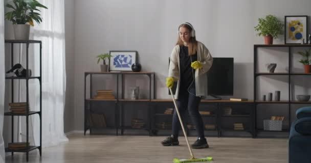 mladá žena uklízí ve dne v moderním bytě, myje podlahu a poslouchá hudbu, zpívá, tančí s mop