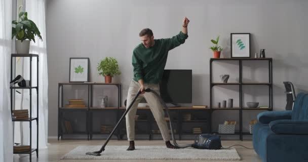 Tanzender Mann saugt Teppich im Wohnzimmer, benutzt Staubsauger, hat Spaß beim Aufräumen