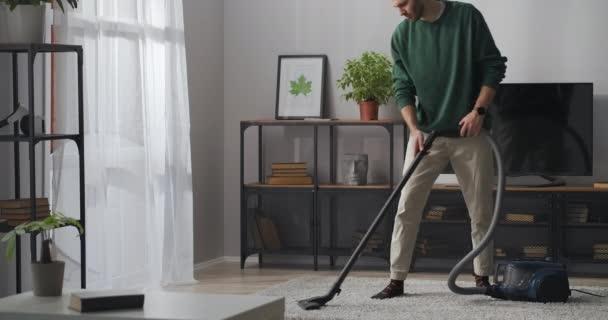 egyedülálló férfi porszívózik szőnyeg a nappaliban, csinál takarítás lakásban hétvégén, agglegény porszívó otthon