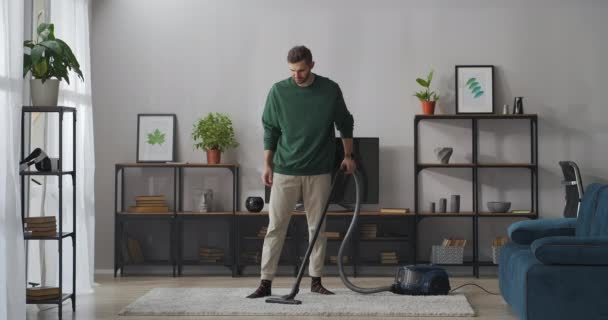 Mann putzt mit Staubsauger im Wohnzimmer der modernen Wohnung, hilft im Haus herum, männlicher Hausbesitzer