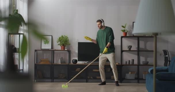 úklid v mládeneckém bytě, mladý radostný muž umývá podlahu a tančí s mopem, poslouchá hudbu