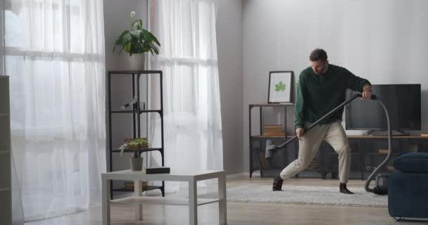 glücklicher Mann putzt in Wohnung und tanzt wie Rockmusiker, spielt auf Staubsauger als Gitarre