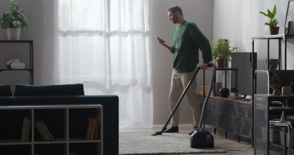 Erwachsener Mann saugt in Wohnung und nutzt Smartphone, schaut soziale Netzwerke an und liest Nachrichten im Web