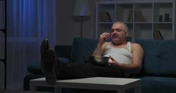 Egy ősz, rövid, ősz hajú férfi néz egy akciófilmet a tévében, és popcornt eszik. Fényes villanás a képernyőn.