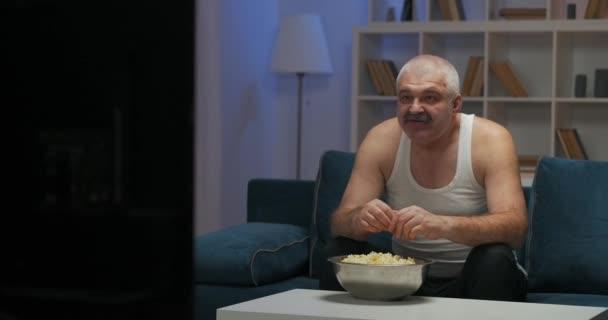 Egy idős, ősz hajú férfi otthoni ruhában nézi kedvenc csapata meccsét a tévében. Pattogatott kukoricát eszem. Tapsolja meg a kezét. Gólt kiáltott és felemelte a kezét..