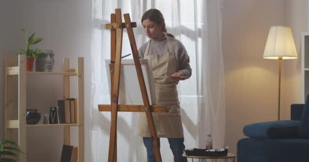 művészi hobbi fiatal nő, hölgy rajz festékek a nappaliban, a festőecset és festőállvány vászon