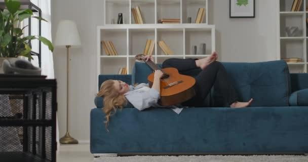 bezstarostná žena hudebnice hraje píseň na kytaru ležící na gauči v domě o víkendu, relaxovat a bavit se doma během uzamčení