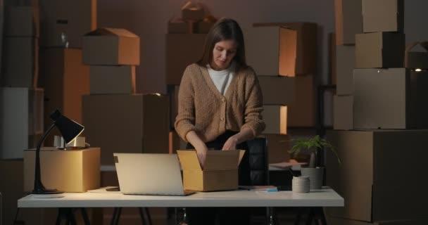 Nachtarbeit in kleinem Lager, Frau packt Karton mit Waren für Kunden und legt Dokumente hinein, mittleres Porträt