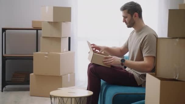 Ein junger Mann öffnet einen Karton und nimmt Dinge heraus, die nach dem Umzug auf dem Sofa in einer neuen Wohnung liegen. Eine neue Wohnung kaufen