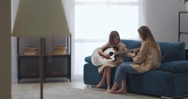 woman and little daughter are spending time together at home, child is learning to play guitar, woman is helping her