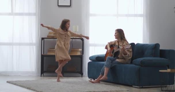 charmantes kleines Mädchen tanzt, Frau spielt Gitarre, Mutter und Tochter haben Spaß zusammen zu Hause, Musik und Tanz