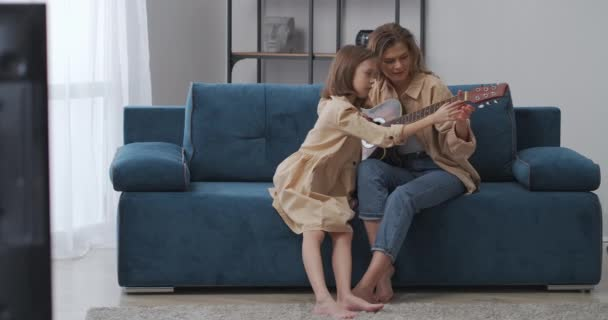 malá holčička se učí hrát na kytaru, žena ji učí doma, o víkendu doma, matka a dítě