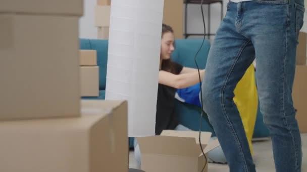 Nettes Mädchen nimmt Dinge aus der Kiste nach dem Umzug in eine neue Wohnung.