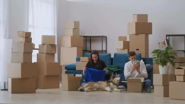 Weitschuss. Ein junger Mann packt aus. Die Frau nimmt die Kleider aus der Kiste und legt sie auf das Sofa. Ein junges Paar zog in ein neues Haus. Die Familie kaufte sich eine neue Wohnung.