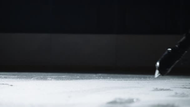 male figure skater is training or performing on ice rink, closeup view of feet shod skates, gliding and jumping