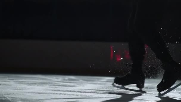 male figure skater is performing steps sequence on ice rink, closeup of feet shod skates, sporty man is training