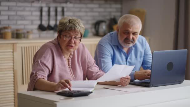 domácí účetnictví, staří manželé platí účty za veřejné služby online, manželka počítá podle staré kalkulačky, manžel platí on-line pomocí moderního notebooku
