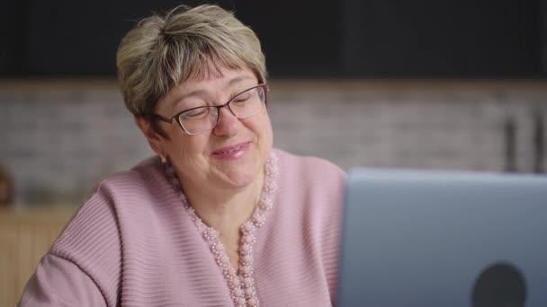 šťastná babička je chatování s rodinou pomocí video chatu v notebooku, důchodce dáma sedí doma kuchyně o víkendu