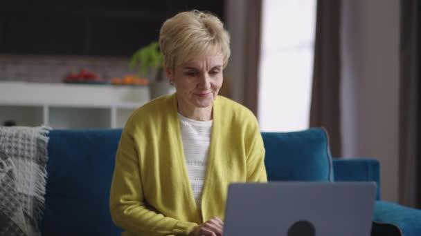 roztomilá stařena si povídá pomocí videohovoru s přáteli nebo rodinou, zůstává doma, sedí na gauči v obývacím pokoji, portrét starší ženy
