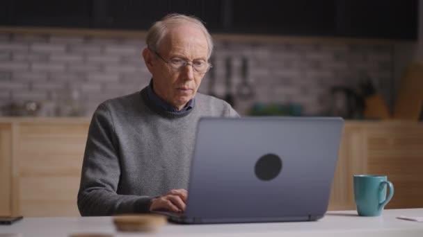 ernster alter Mann arbeitet zu Hause mit Laptop, surft im Internet und sucht nach Informationen, liest Nachrichtenband