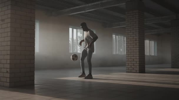 Teenager boy football soccer player practicing tricks, kicks and moves with ball inside empty covered parking garage. Urban city lifestyle outdoors concepte