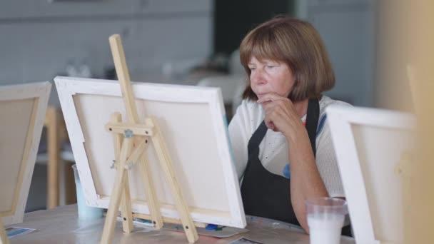 Eine ältere Frau zeichnet ein Bild in einem Malkurs