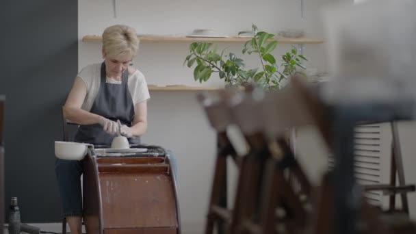 Ältere Handwerkerin arbeitet an einer Töpferscheibe zur Herstellung von Ton- und Keramikkrügen und Tellern in Zeitlupe