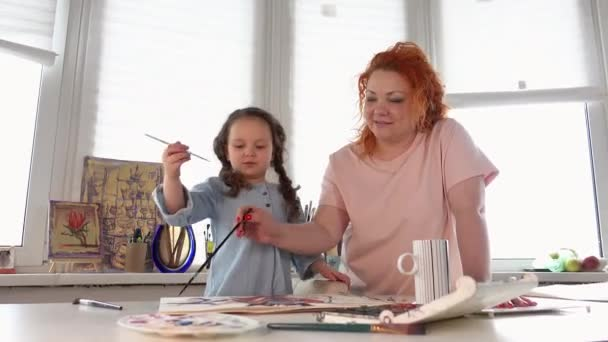 Happy mom helps daughter to draw using watercolor in studio