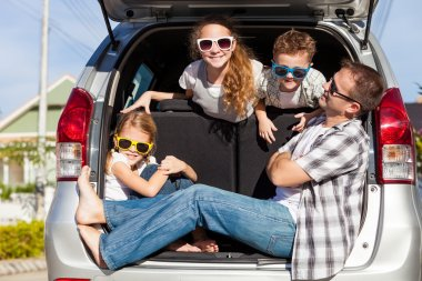 Happy family getting ready for road trip on a sunny day.