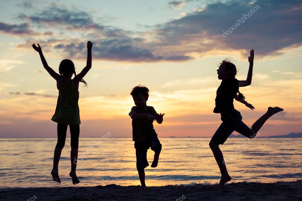 Niños Felices Jugando En La Playa En El Atardecer