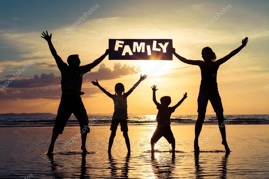 Silueta De Familia Feliz Que De Pie En La Playa De Los