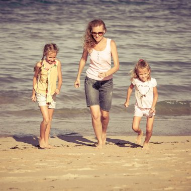 mother and  two daughters playing on the beach