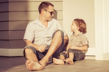 Dad and son playing near a house
