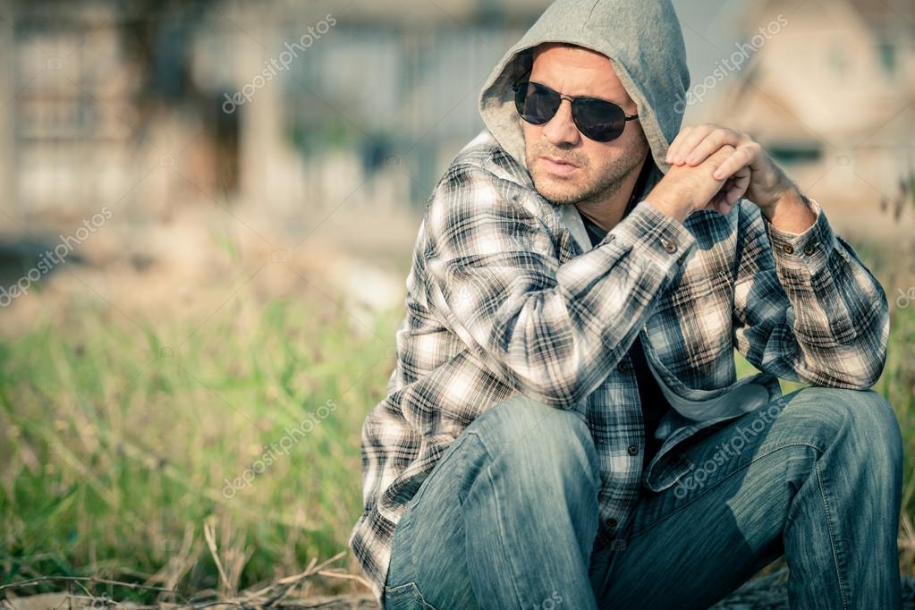 27c8f22bb88e Portrait of a one sad man in sunglasses sitting outdoors near the house at  the day time — Photo by ...
