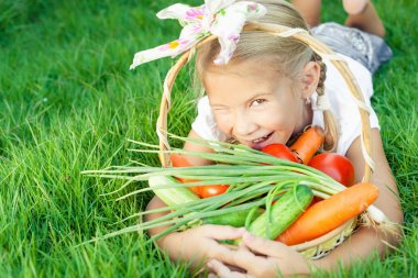 Happy little girl lying on the grass with a basket of vegetables