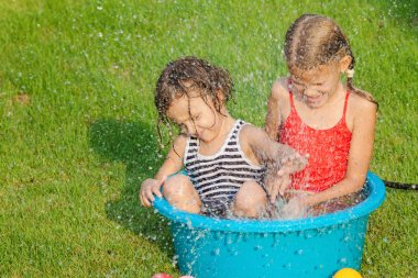 brother and sister playing with water near a house