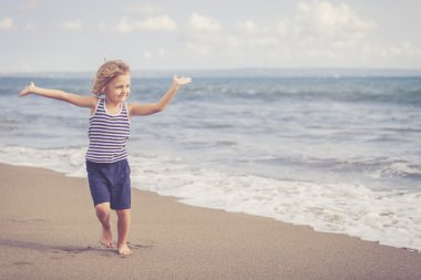 Portrait of little boy jumping on the beach