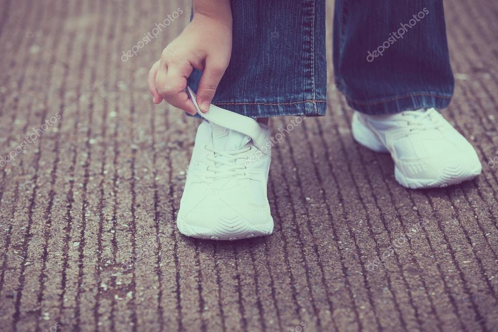 zapatillas juveniles en las piernas de la chica en el camino — Foto ...