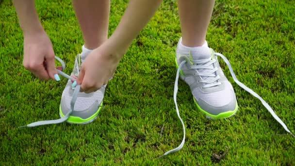 dívka přestala, běh uvázat tkaničky na běžecké boty. venkovní trénink fitness dívka